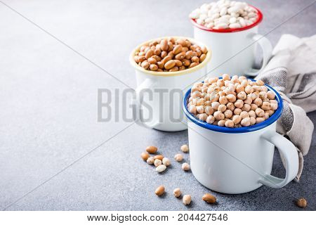 Raw uncooked organic chickpeas and kidney beans in white enamel mugs on rustic wooden board on light gray stone background. Healthy vegan vegetarian food concept with copy space.