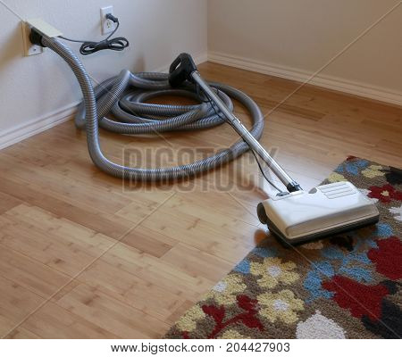 Cleaning contest: Beautiful bamboo hardwood floor and wool rug with a central vacuum cleaner attached to the wall