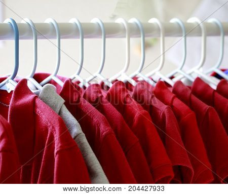 Red and one gray school uniform shirts on hangers. Selective focus.
