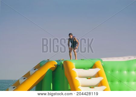 a boy in a life jacket jumps into the water toboggan