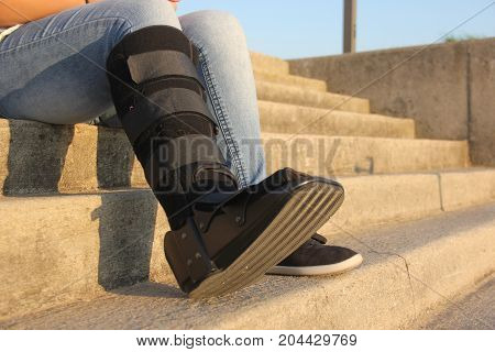 A woman with a walking cast boot siting on the stairs