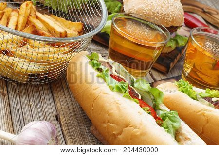 Hot Dogs, Different Snacks And Beer On A Wooden Table, Close-up. National Day Hot Dog Usa