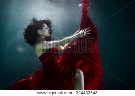 Beautiful woman swimming underwater with elegant dress