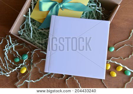 cardboard box is opened with a gift book with white color and candy and paper shavings