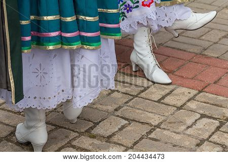 Two women wearing white stage boots. Woman foot takes a step on the street. Women legs and feet with boots in close-up.