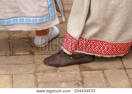 Two women shod in leather shoes handmade. The girls are dressed in linen dresses with ornament. A woman steps foot on the street.