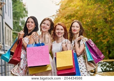 Portrait of four happy girlfriends walking with paperbags after shopping