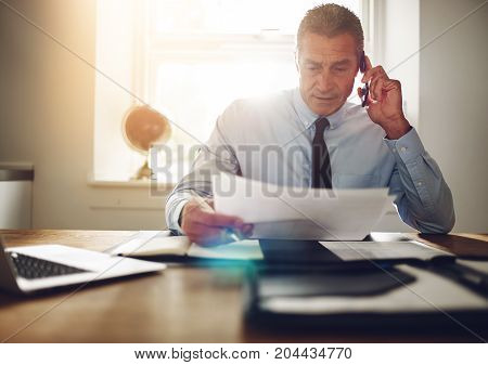 Executive Sitting At A Desk Discussing Paperwork On The Phone