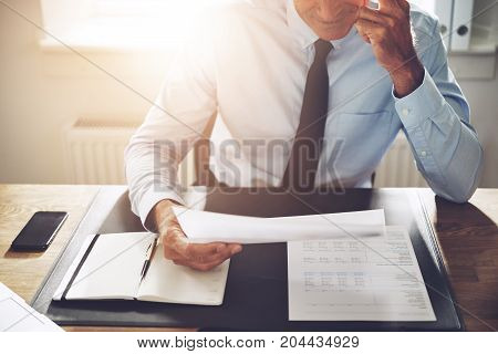 Mature Businessman Reading Paperwork At His Office Desk