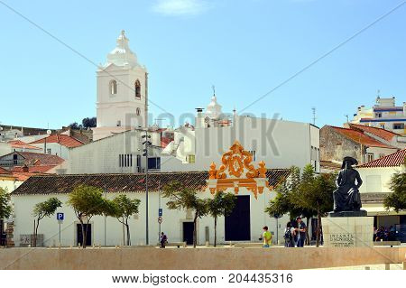 Lagos Algarve Portugal - October 28 2015 : The historical Santa Maria Church bell tower in the background and the Statue of Henry the Navigator in the foreground in Lagos center
