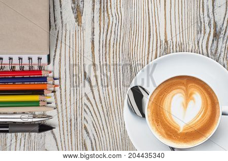 notebook with pencils and graphic tablet with coffee on a wooden background