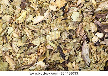 Pile of dry crumbled plantain Plantago lanceolata medicinal herb.