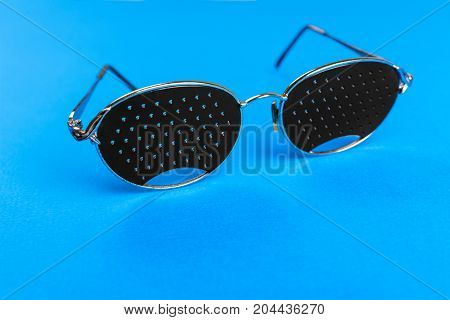 Glasses trainers. Black pinhole glasses on blue background. Medical concept. Top view.