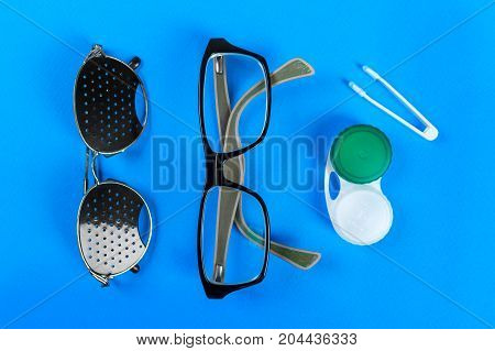 A set of accessories for sight. Medical concept. Pinhole glasses lenses with container and glasses for sight. Top view.