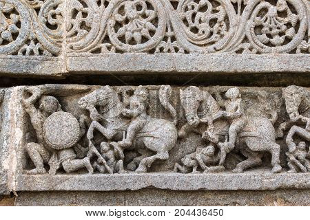 Mysore India - October 27 2013: Close up of frieze on outside wall of central shrine called Trikuta at Chennakesave temple in somanathpur. Warriors on horses fighting men on foot.