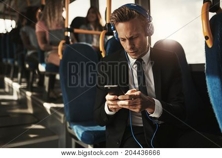 Young Businessman Wearing Headphones And Reading Texts On A Bus