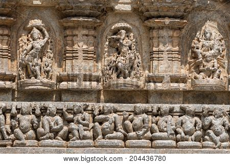 Mysore India - October 27 2013: Stone frieze with heavily damaged statues on outside wall of central shrine called Trikuta at Chennakesave temple in somanathpur. Line of sitting men deities.
