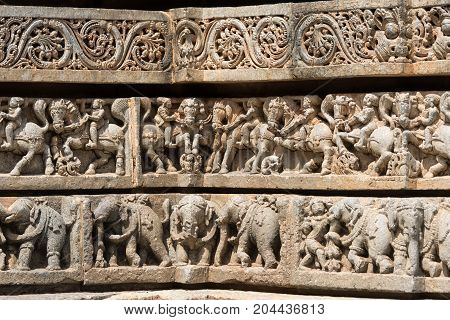 Mysore India - October 27 2013: Series of three friezes on outside wall of central shrine called Trikuta at Chennakesave temple in somanathpur. Warriors on horses elephants decorative.
