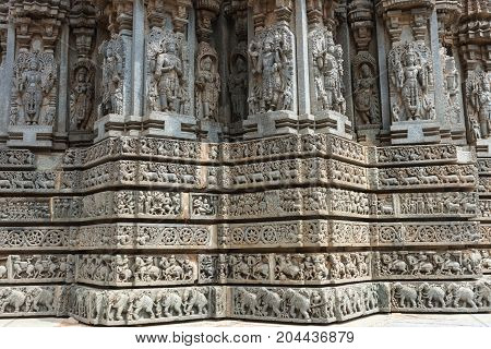 Mysore India - October 27 2013: Stone corner friezes with deity statues on outside wall of central shrine called Trikuta at Chennakesave temple in Somanathpur.