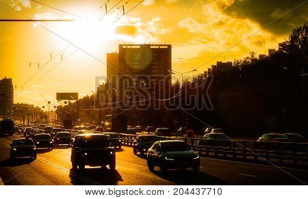 Cars moving in city at sunset against the sun background