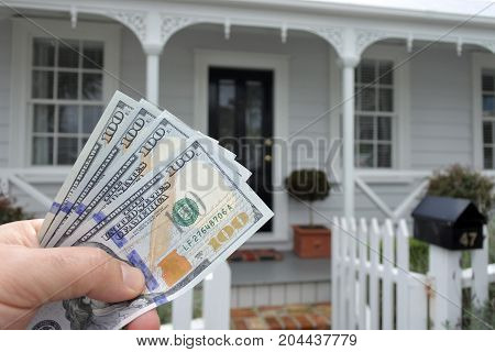 A Mans Hand Holds Us Dollar Bills Against A Front Of North American House
