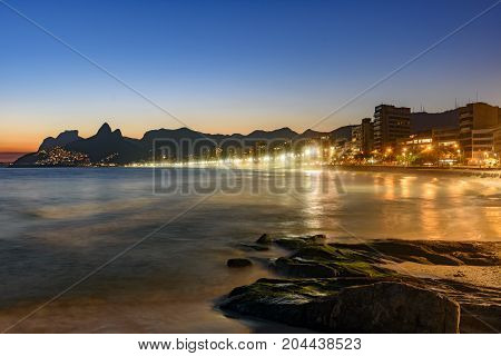 Ipanema beach with beautiful skyline and sunset. City lights and buildins araoud the ocean