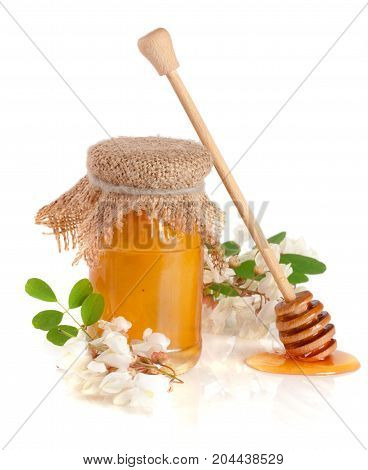 Jar of honey with flowers of acacia isolated on white background.