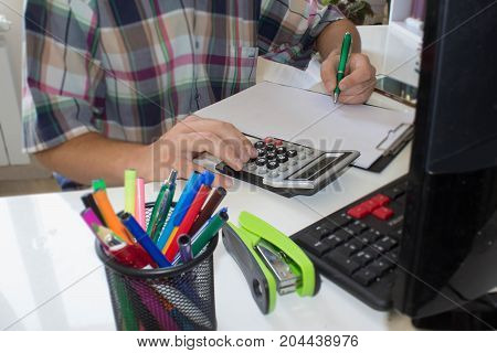 Businessman accountant working at office desk he is using a calculator and pen.