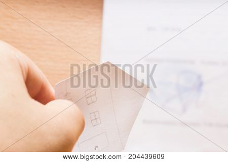 acute triangular roof of a paper house in hand points to a signature with a stamp of the real estate market concept