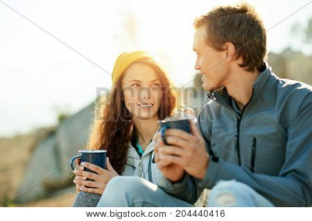 Smiling young couple sitting on a rock talking and drinking coffee together while taking a break from a hike in the wilderness