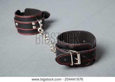 Black Leather Handcuffs On Gray Background. Sex Toy.