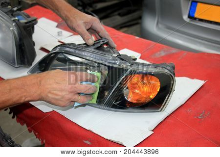 Man refurbishing a car headlight with clear coating
