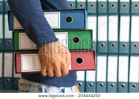 Man holding corporate files in document binder.