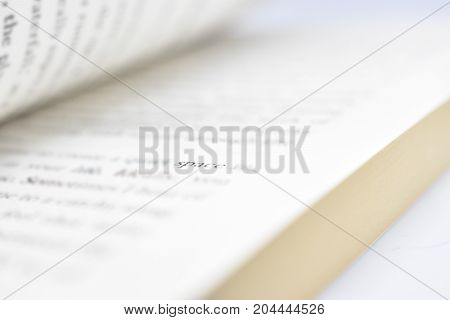 Close up bokeh of open book pages illustrating writing, education or creativity