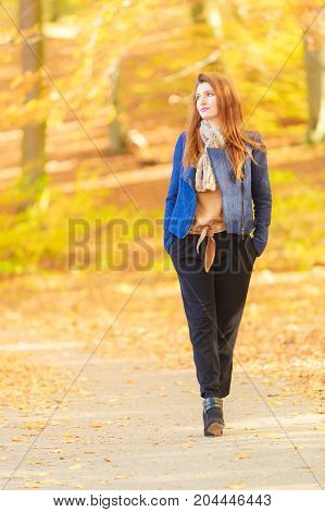 Modest girl in park. Fashionable young woman taking walk. Fashion relax nature concept.