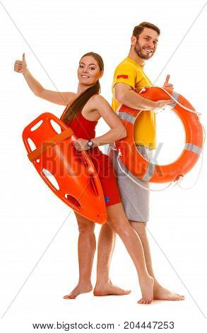 Lifeguards with rescue tube and ring buoy lifebuoy showing thumb up gesture. Man and woman supervising swimming pool. Accident prevention.