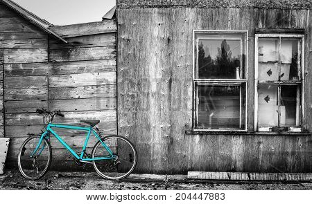 horizontal black and white image of a color selected blue bike leaning an old abandoned wood building with double windows.