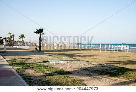 Empty Off Season Finikoudes Beach With Folded Umbrellas In Larnaca
