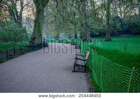 Walking path with many benches in St James Park early in the morning London England