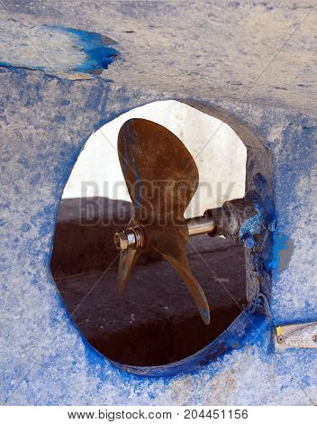 propeller on an old blue traditional fishing boat or trawler in dry dock in spain