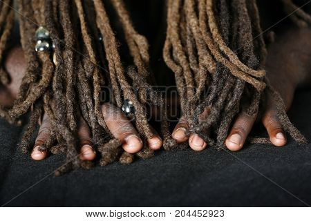 Close up of hands of African-American man holding dreadlocks
