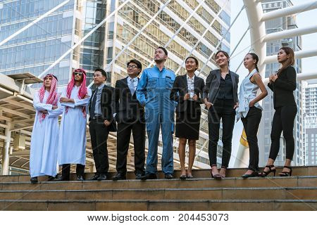 Multicultural business people group including Arabic East Asian Latin American standing in modern city. Concept of multi ethnic multiracial business team.