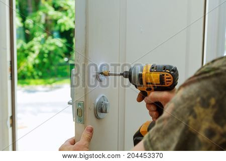 Installation locked interior door knobs close-up woodworker hands install lock. installation of a lock at the door