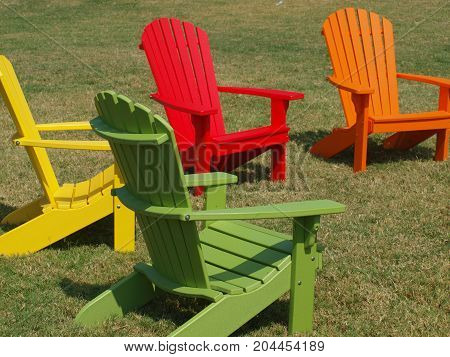 Multi-colored Slat-back chairs on a lawn in a newly cleared lot of buildings.