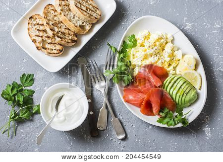 Healthy balanced breakfast or snack - smoked salmon egg salad and avocado. On a gray background top view. Healthy food concept