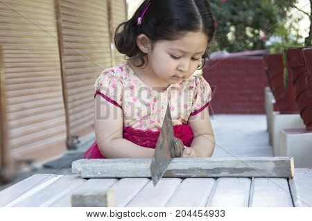 Little girl carpenter sawing wood plank with a handsaw outdoors. Indian, Asian.