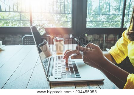 Side view of charming young hipster girl hands using on her smart phone sitting at wooden table in a coffee shop. woman using laptop in a cafe - vintage color style.