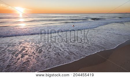 Aerial of a surfer wading into the ocean surf with a colourful sunrise sky.