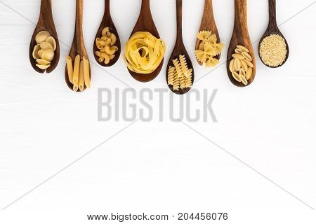 Pasta selection of penne gnocci rigatoni casarecce fiorelli pasta Farfalle pasta A Riso Orecchiette Pugliesi Gnocco Sardo and Farfalle in wooden spoons over white background