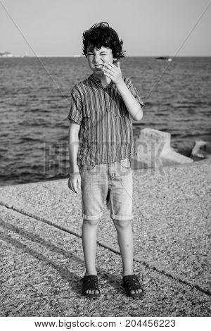 A disgruntled boy is standing by the sea. Black and white.